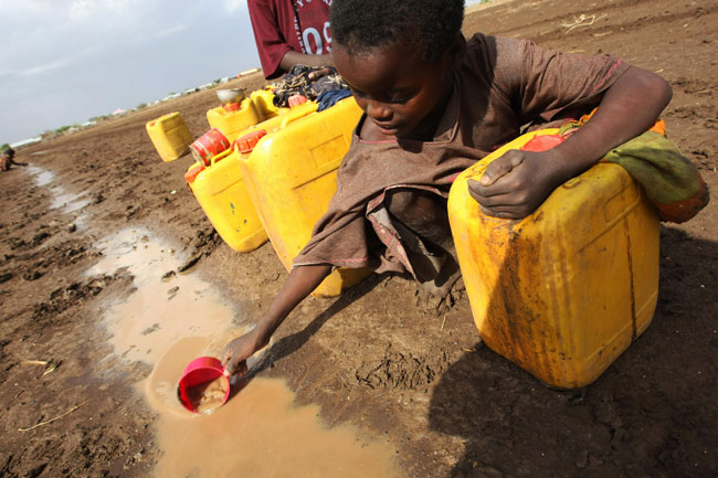 Kid in Africa filling water can