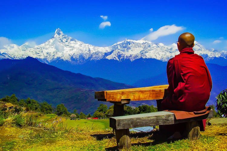 Buddhist Monk looking at the Annapurna Peak in Nepal
