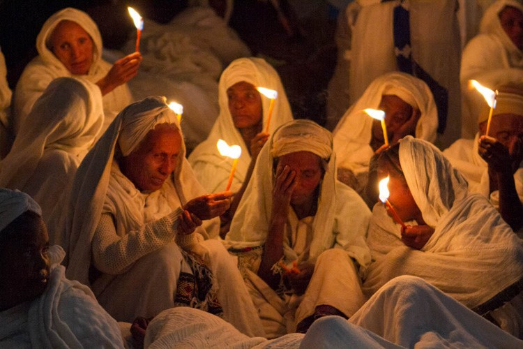 Praying with candles in a church in Lalibela, Ethiopia, Africa.