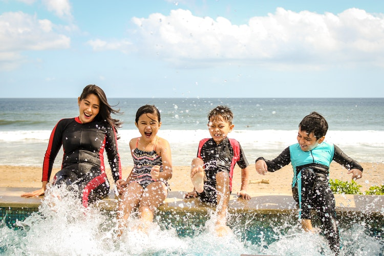A mother with her three children, splashing in a swimming pool next to a beach.