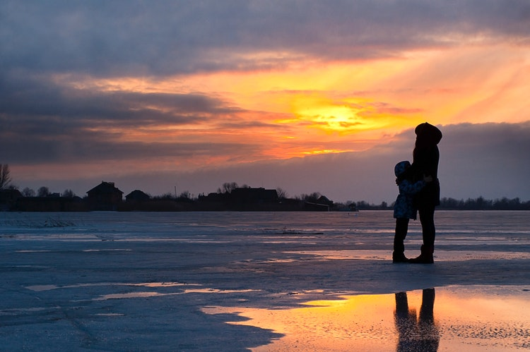 Mother and child standing on the shore of a snowy beach at sunset