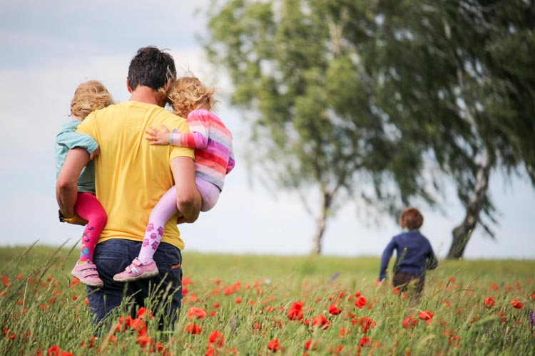 Father with children walking in the fields